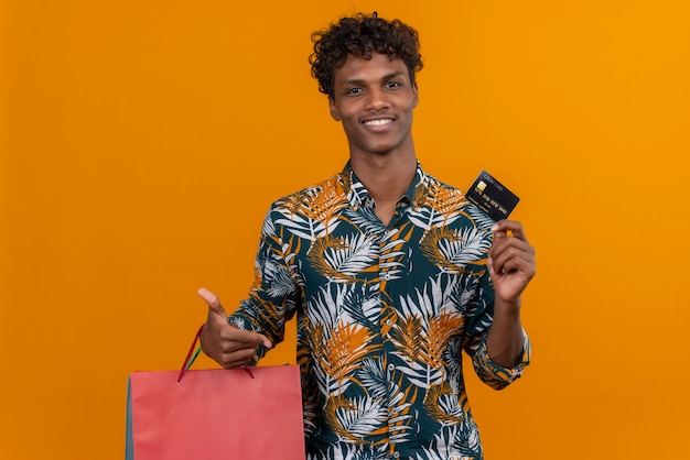 葉の巻き毛を持つ満足している若いハンサムな浅黒い肌の男がオレンジ色の背景の上に立っている間クレジットカードを示すプリントシャツsmileingholdingショッピングバッグを印刷