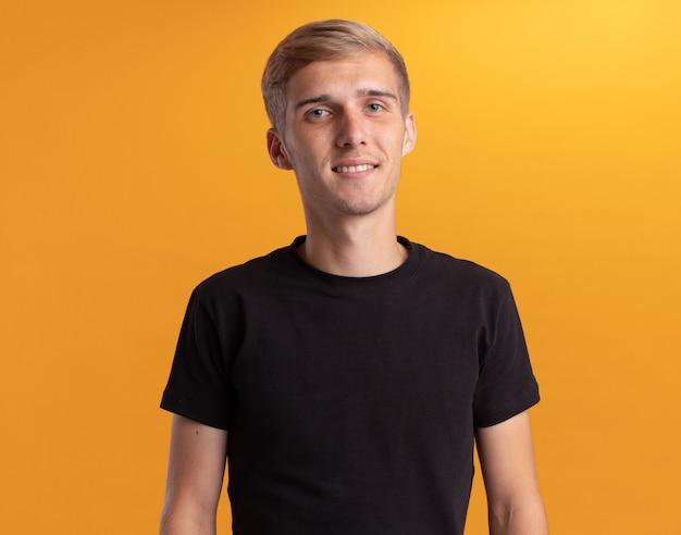 Soddisfatto giovane bel ragazzo che indossa la camicia nera isolata sul muro giallo