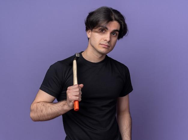 Lieto giovane bel ragazzo che indossa la maglietta nera che mette il martello sulla spalla isolata sulla parete viola