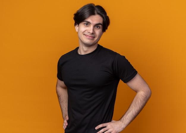 오렌지 벽에 고립 된 엉덩이에 손을 댔을 검은 티셔츠를 입고 기쁘게 젊은 잘 생긴 남자