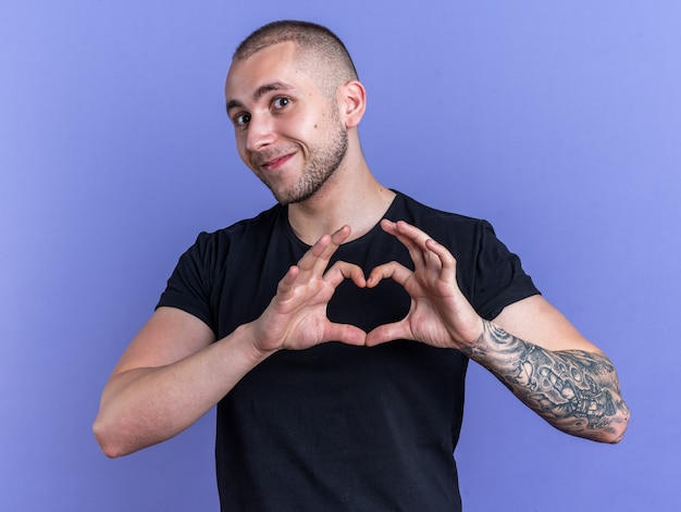 파란색 배경에 고립 된 심장 제스처를 보여주는 검은 티셔츠를 입고 기쁘게 젊은 잘 생긴 남자