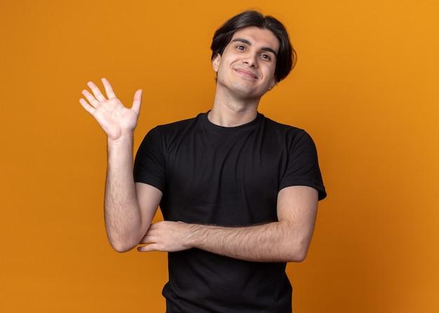 オレンジ色の壁に分離されたこんにちはジェスチャーを示す黒い t シャツを着た若いハンサムな男が喜んで