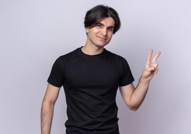 흰 벽에 고립 된 평화 제스처를 보여주는 검은 티셔츠를 입고 기쁘게 젊은 잘 생긴 남자