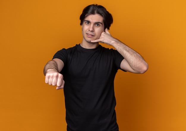 Довольный молодой красивый парень в черной футболке показывает жест телефонного звонка и протягивает кулак впереди изолирован на оранжевой стене