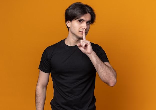 복사 공간 오렌지 벽에 고립 된 침묵 제스처를 보여주는 검은 티셔츠를 입고 기쁘게 젊은 잘 생긴 남자