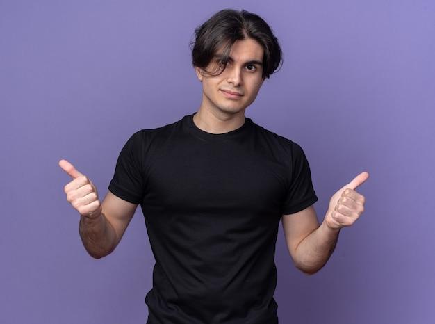 보라색 벽에 고립 된 엄지 손가락을 보여주는 검은 티셔츠를 입고 기쁘게 젊은 잘 생긴 남자