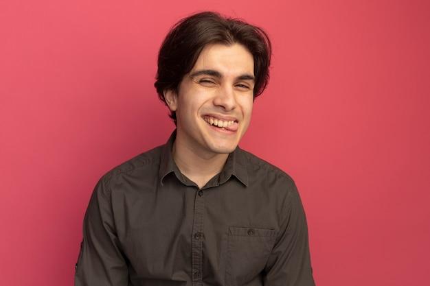 분홍색 벽에 고립 된 혀를 보여주는 검은 티셔츠를 입고 기쁘게 젊은 잘 생긴 남자