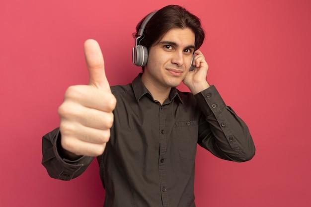 분홍색 벽에 고립 엄지 손가락을 보여주는 헤드폰으로 검은 티셔츠를 입고 기쁘게 젊은 잘 생긴 남자
