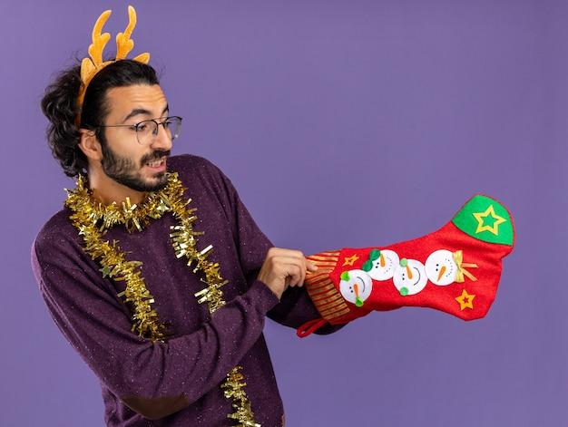 Довольный молодой красивый парень в рождественском обруче для волос с гирляндой на шее держит и кладет руку в рождественские носки, изолированные на синем фоне
