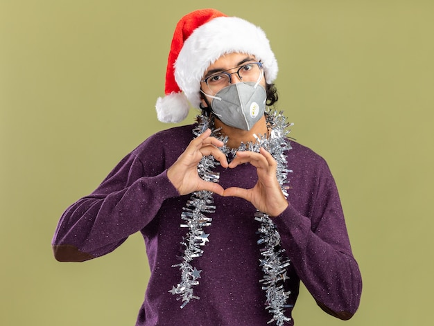 オリーブ グリーンの壁に心のジェスチャーを示す首に花輪とクリスマスの帽子と医療マスクを着て喜んで若いハンサムな男
