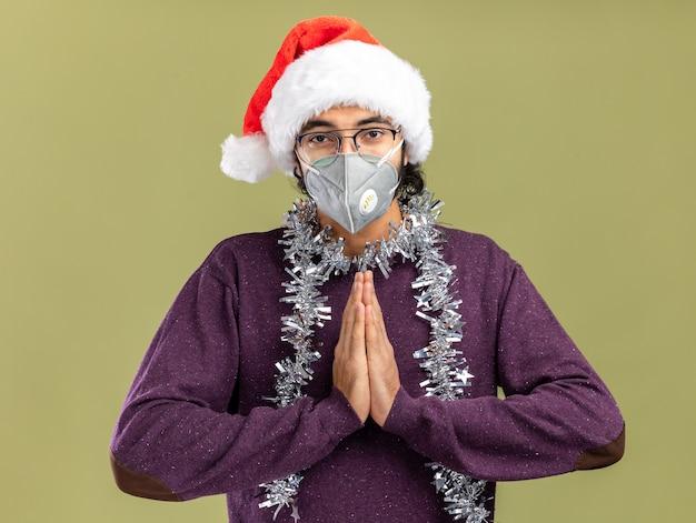 Довольный молодой красивый парень в новогодней шапке и медицинской маске с гирляндой на шее показывает жест молитвы, изолированный на оливково-зеленой стене