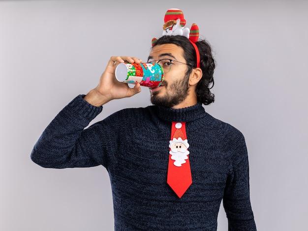 Lieto giovane bel ragazzo che indossa cravatta natalizia con il cerchio dei capelli beve dalla tazza di natale isolato su sfondo bianco