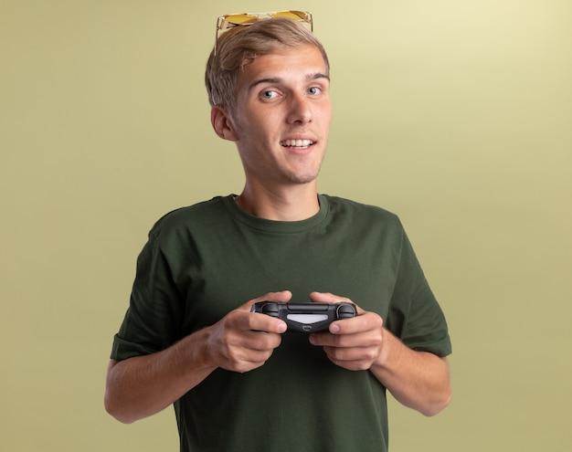 Soddisfatto giovane bel ragazzo che indossa una camicia verde con gli occhiali sulla testa che gioca sul joystick del controller di gioco isolato sulla parete verde oliva