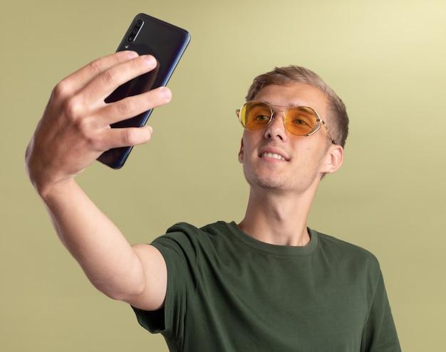 緑のシャツを着て眼鏡をかけた若いハンサムな男が、オリーブ グリーンの壁に自撮りをする