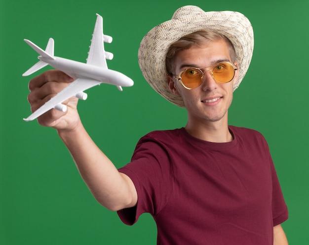 Lieto giovane bel ragazzo che indossa la camicia rossa e occhiali con il cappello che tiene fuori l'aeroplano giocattolo nella parte anteriore isolata sulla parete verde