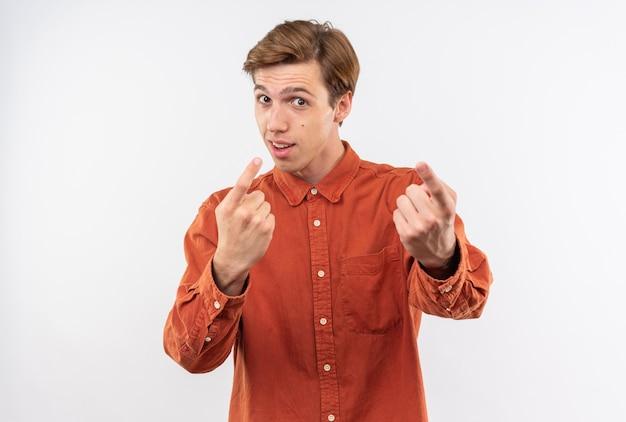Il giovane bel ragazzo contento che indossa una maglietta rossa indica la telecamera