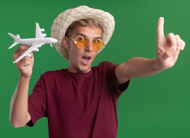 Lieto giovane bel ragazzo indossa una camicia rossa con gli occhiali e il cappello che tiene aeroplano giocattolo tendendo il dito alla macchina fotografica isolata sulla parete verde
