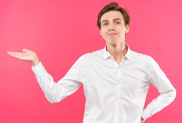Довольный молодой красивый парень в белой рубашке притворяется, что держит что-то изолированное на розовой стене