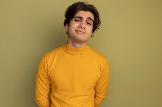 コピースペースとオリーブグリーンの壁に分離された黄色のタートルネックのセーターを着て満足している若いハンサムな男