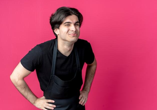 コピースペースでピンクに分離された腰に手を置く制服を着た若いハンサムな男性理髪師を喜ばせる