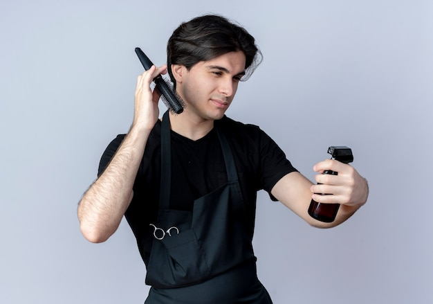 Pleased young handsome male barber in uniform holding comb around head and looking at spray bottle in his hand isolated on white wall