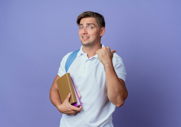 Pleased young handsome male student wearing back bag holding books and points side isolated on blue