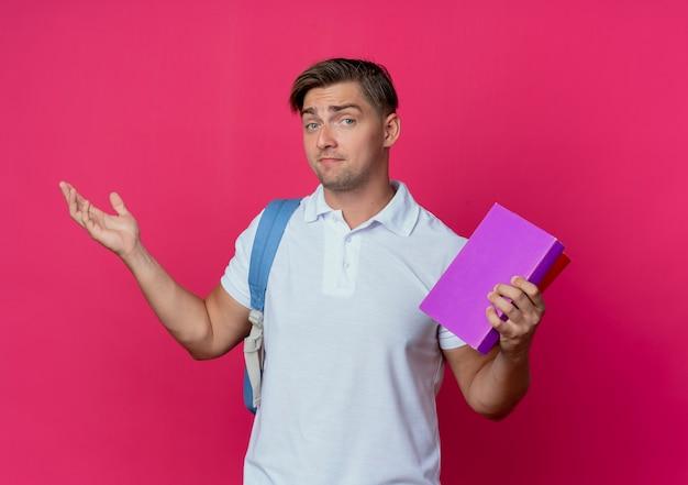 Soddisfatto giovane studente maschio bello che porta i libri della holding della borsa posteriore