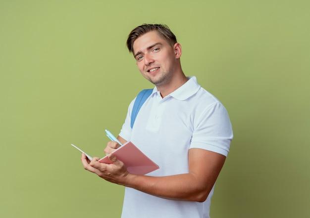 オリーブグリーンの背景で隔離のノートに何かを書くバックバッグを身に着けている若いハンサムな男子学生を喜ばせる