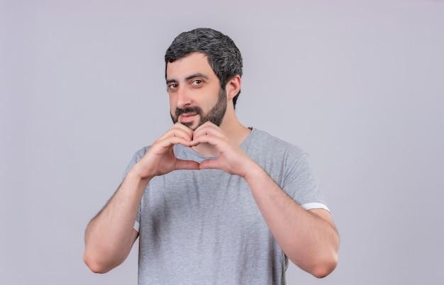 Lieto giovane uomo bello che fa il segno del cuore nella parte anteriore isolato sul muro bianco