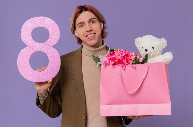 Pleased young handsome man holding pink number eight and gift bag with flowers and teddy bear