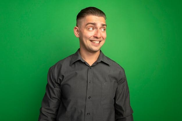 緑の壁の上に立っている顔に大きな笑顔で脇を見て灰色のシャツを着た若いハンサムな男を喜ばせる