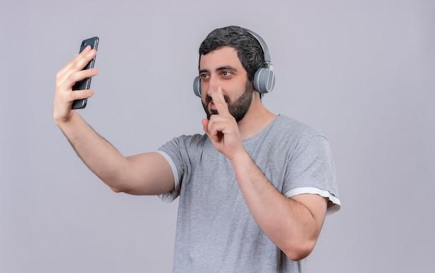 ピースサインをし、白い壁に隔離された携帯電話でselfieを取るヘッドフォンを身に着けている若いハンサムな男を喜ばせる