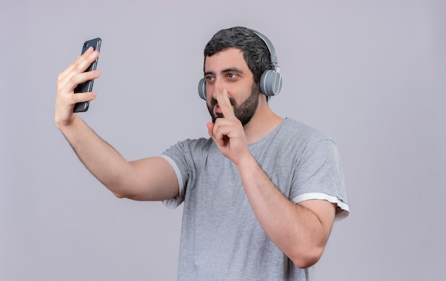 Lieto giovane uomo bello che indossa le cuffie facendo segno di pace e prendendo selfie con il telefono cellulare isolato sul muro bianco
