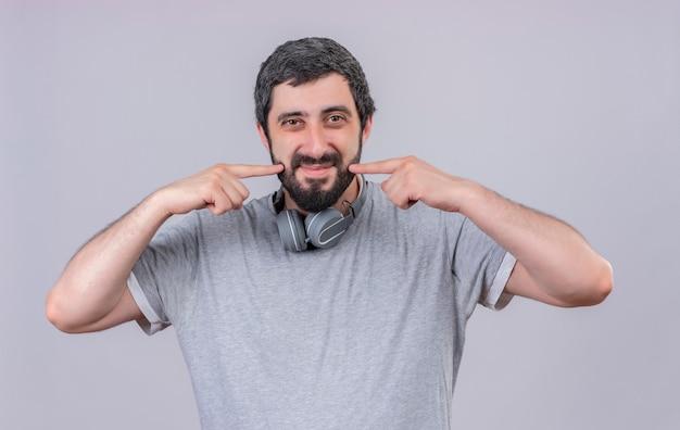 首にヘッドフォンを着用し、白い壁に隔離された彼の笑顔を指して喜んで若いハンサムな男