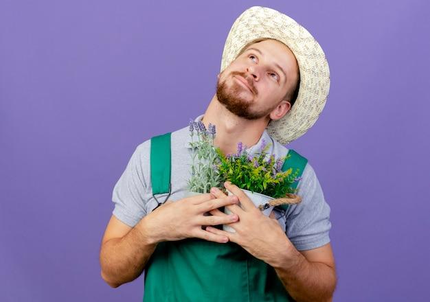 Довольный молодой красивый славянский садовник в униформе и шляпе держит цветочные горшки, глядя вверх, погружаясь в мечты, изолированные на фиолетовой стене с копией пространства