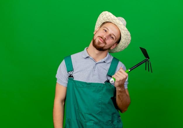 Довольный молодой красивый славянский садовник в униформе и шляпе с граблями смотрит