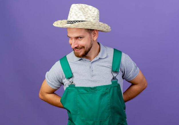 コピースペースで紫色の壁に隔離された背中の後ろに手を保つ制服と帽子の若いハンサムなスラブの庭師を喜ばせる