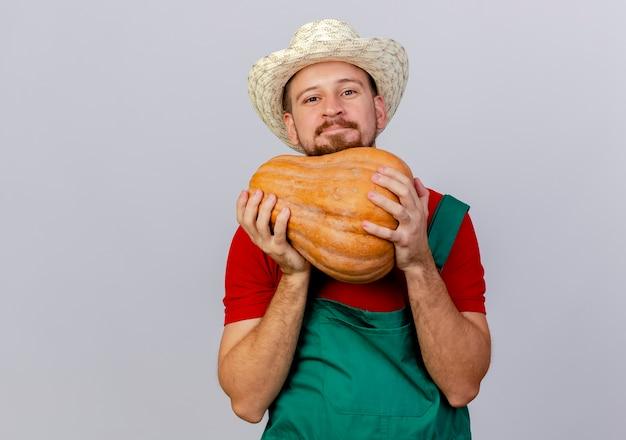 Felice giovane giardiniere slavo bello in uniforme e cappello che tiene zucca butternut cercando isolato