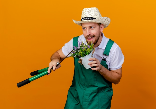 Pleased young handsome slavic gardener in uniform and hat holding flowerplant and pruners looking up isolated
