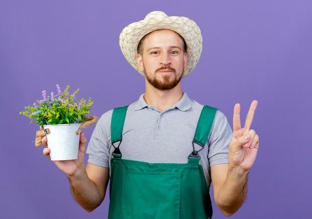 Felice giovane giardiniere slavo bello in uniforme e cappello che tiene vaso di fiori cercando di fare segno di pace isolato sulla parete viola