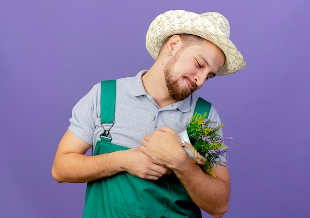 Felice giovane giardiniere slavo bello in uniforme e cappello tenendo e guardando il vaso di fiori isolato sulla parete viola con lo spazio della copia