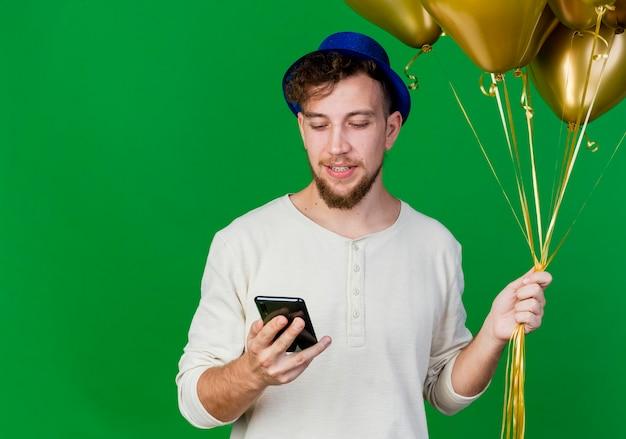 Довольный молодой красивый славянский тусовщик в партийной шляпе, держащий воздушные шары и мобильный телефон, смотрящий на телефон, изолированный на зеленом фоне с копией пространства