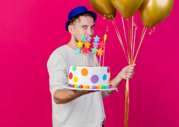 행복 한 젊은 잘 생긴 슬라브 파티 남자 풍선을 들고 앞쪽으로 생일 케이크를 뻗어 파티 모자를 쓰고 복사 공간이 분홍색 벽에 고립 된 정면을보고