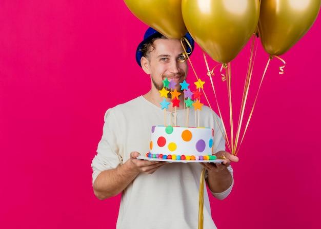 Felice giovane ragazzo slavo bello del partito che indossa il cappello del partito che tiene i palloncini e la torta di compleanno con le stelle che esaminano davanti isolato sulla parete rosa con lo spazio della copia