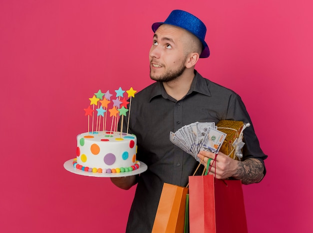 Pleased young handsome slavic party guy wearing party hat holding birthday cake money gift pack and paper bags turning head to side looking up isolated on crimson background with copy space