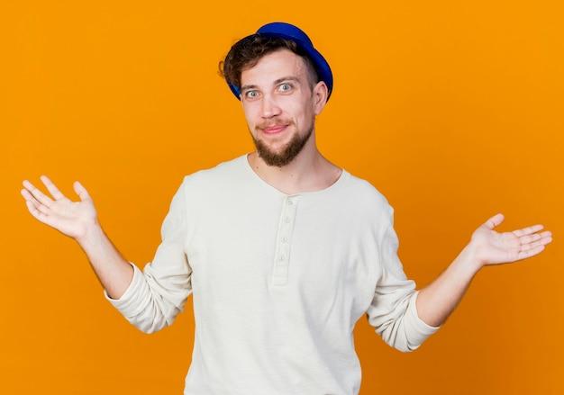 Felice giovane bel partito slavo ragazzo che indossa il cappello del partito che guarda l'obbiettivo che mostra le mani vuote isolate su sfondo arancione