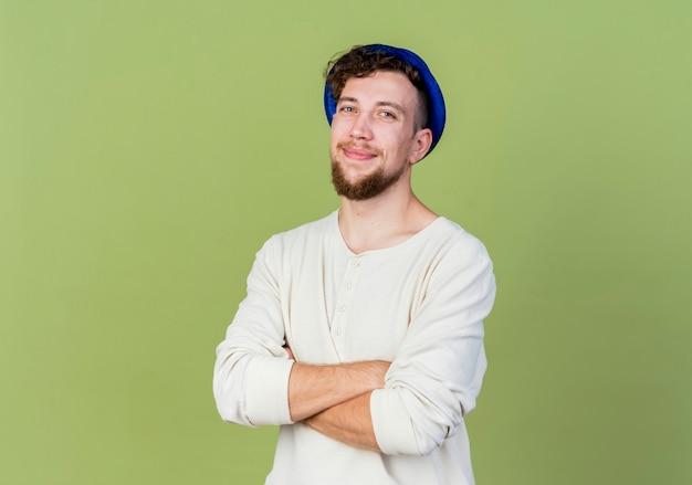 コピースペースでオリーブグリーンの背景に分離されたカメラを見て閉じた姿勢で立っているパーティーハットを身に着けている若いハンサムなスラブ党の男を喜ばせる