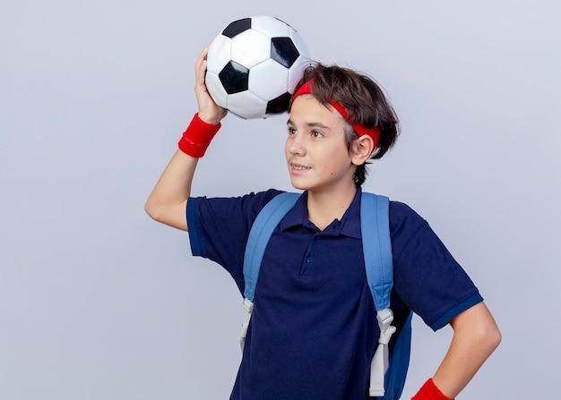 Felice giovane bel ragazzo sportivo guardando dritto toccando la testa con il pallone da calcio
