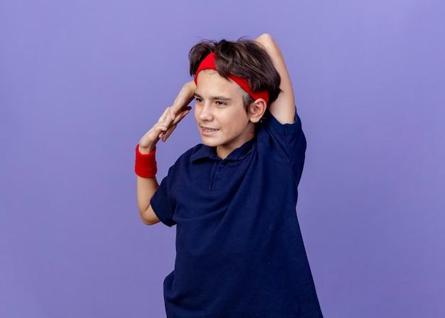 ヘッドバンドとリストバンドを身に着けている若いハンサムなスポーティな少年は、コピースペースで紫色の背景に分離された運動をしている首の後ろで手を一緒に保つ側を見て歯のブレースで喜んでいます