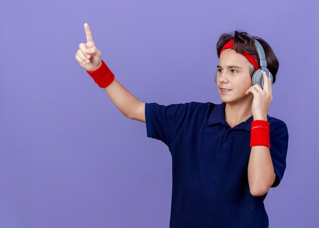 Pleased young handsome sporty boy wearing headband and wristbands and headphones with dental braces looking at side touching headphones pointing up isolated on purple background with copy space